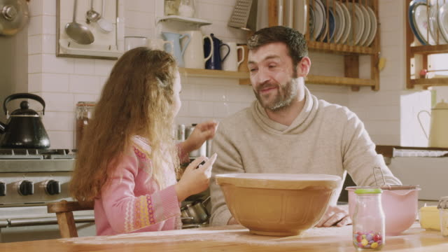 vidéos et rushes de cu shot of daddy & daughter play while seiving flour in kitchen / london, united kingdom  - espièglerie