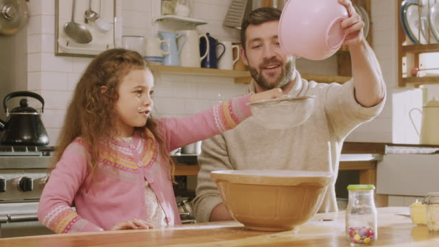 stockvideo's en b-roll-footage met ms shot of daddy & daughter sieving flour in kitchen / london, united kingdom  - bakken
