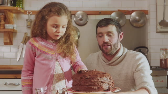 cu shot of daddy sitting and daughter standing at kitchen table adding chocolate icing to cake / london, united kingdom  daddy giving advice / london, united kingdom  - daughter stock videos & royalty-free footage