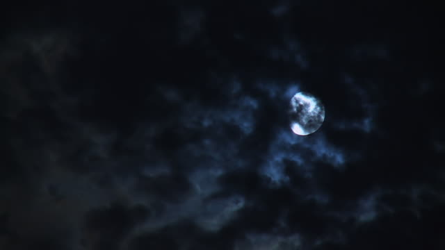 ms t/l shot of dark clouds passing across moon at night / london, united kingdom  - moon stock videos & royalty-free footage