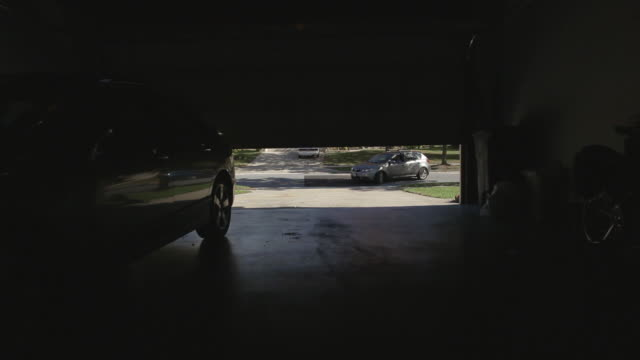 MS Shot of dark screen garage, car coming for parking / Laurell, Maryland, United States