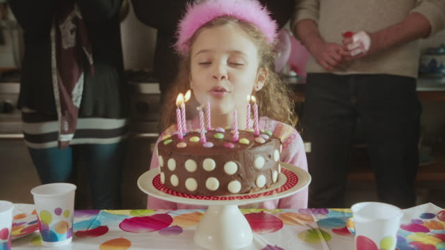 vídeos de stock, filmes e b-roll de cu shot of daughter blowing out candles on her chocolate birthday cake with balloons and party poppers / london, united kingdom  - aniversário