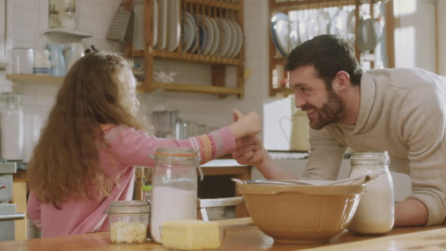 vidéos et rushes de cu shot of daughter in kitchen gets ingredients for baking then daddy talks to her / london, united kingdom  - angleterre