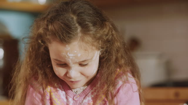cu shot of daughter smiling with flour on her face while daddy through flour into air / london, united kingdom  - daughter stock videos & royalty-free footage