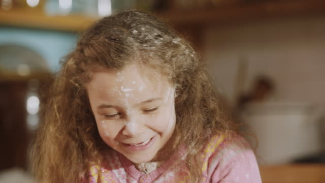 cu shot of daughter smiling with flour on her face while daddy through flour into air / london, united kingdom  - flour stock videos & royalty-free footage