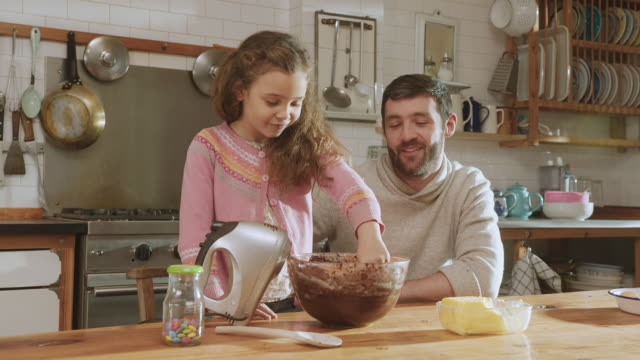 ms shot of daughter sticking finger in cake mix, trying it and nodding with approval / london, united kingdom  - peluria del viso video stock e b–roll
