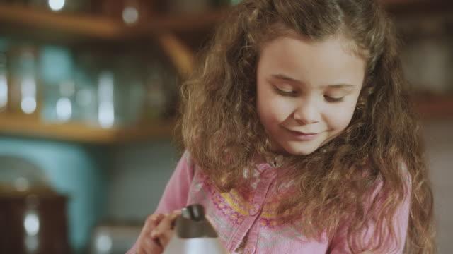 CU TU TD Shot of daughter whisking cake mix in bowl / London, United Kingdom