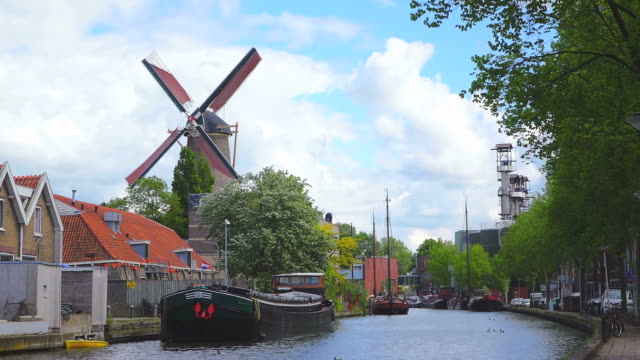 ws shot of de roode leeuv windmill / gouda, south holland, netherlands - zona pedonale strada transitabile video stock e b–roll