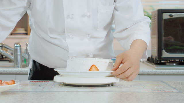 Shot of decorating cake with strawberry