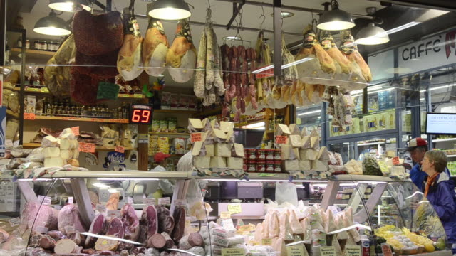 ms shot of delicatessen shop with salami, cheese and ham in ambrogio market / florence, tuscany, italy - デリカッセン点の映像素材/bロール