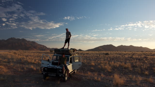 ms t/l shot of desert campers survey landscape from roof of all terrain vehicle towards dusk with mountains in back side / naukluft, windhoek, namibia - stationary stock videos & royalty-free footage