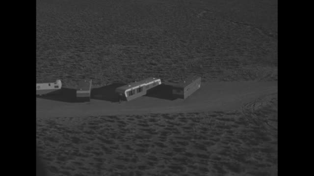 Shot of desert landscape at Yucca Flat / two aerial shots of sheds and trailers at bomb site / concrete building withstands blast from explosion /...
