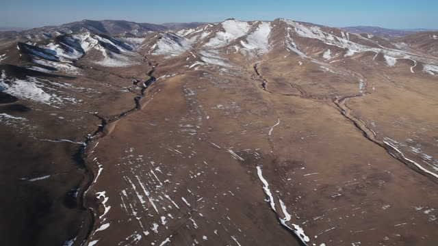 vidéos et rushes de ws aerial shot of desert lanscape with big hills and small mountains covered partially in snow / suhbaatar, mongolia, mongolia - désert de gobi
