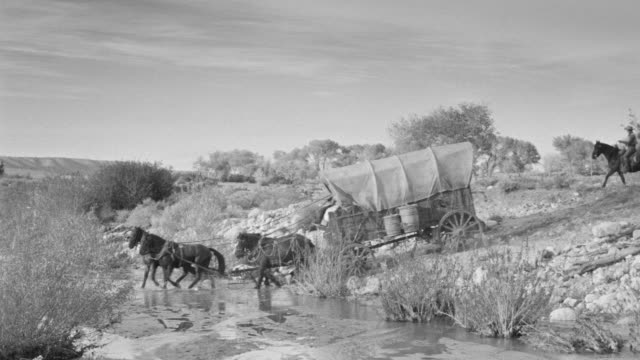 WS PAN Shot of desert to follow wagon train traveling through riverbed