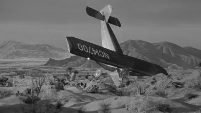MS Shot of desert with mountains and plane making crash landing (miniature)