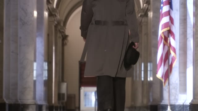 MS LA R/F Shot of Detective in trench coat walking down marble hallway with American flag / United States