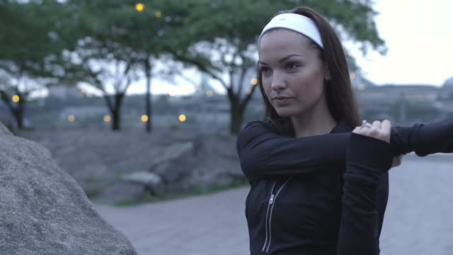 mcu shot of determining young woman as she stretches and prepares for her morning jog before dawn on city water front / portland, oregon, united states  - hair accessory stock videos and b-roll footage