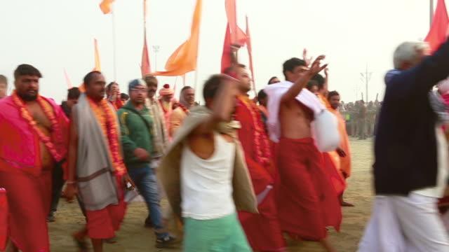 ms pan shot of devotee and sadhus walking in kumbh mela / allahabad, uttar pradesh, india - braccio umano video stock e b–roll