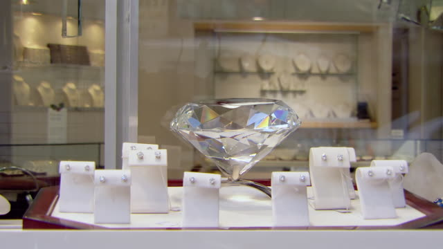 CU Shot of Diamond earrings on display on models in store window as people walking / Philadelphia, Pennsylvania, United States