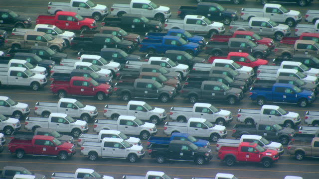stockvideo's en b-roll-footage met cu aerial ts shot of different colored f150 trucks parked on parking lot on overcast day / dearborn, michigan, united states - made in the usa korte frase
