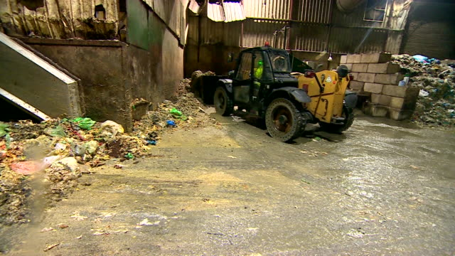Shot of digger scooping up and depositing food waste into loading bay