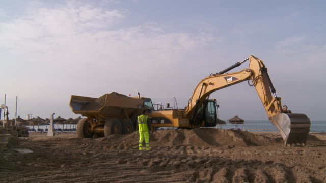 vidéos et rushes de ws shot of digging machine loading sand in truck to restored public beach / marbella, andalusia, spain - creuser