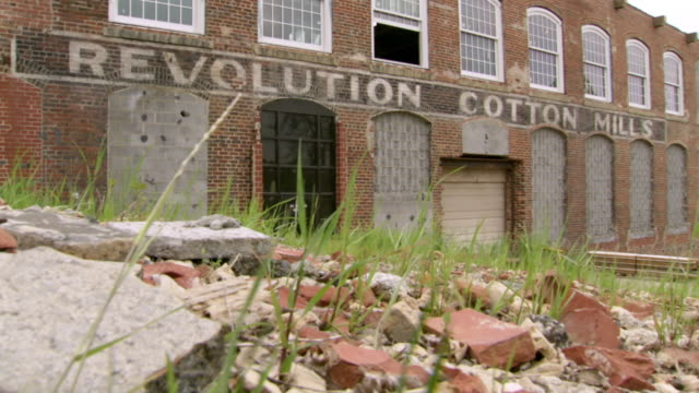 MS Shot of dilapidated facade of Revolution Cotton Mills with rubble and grass / Greensboro, North Carolina, United States
