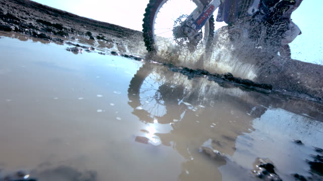 MS SLO MO Shot of dirt bike riding through puddle and splashing mud / Venice, California, United States
