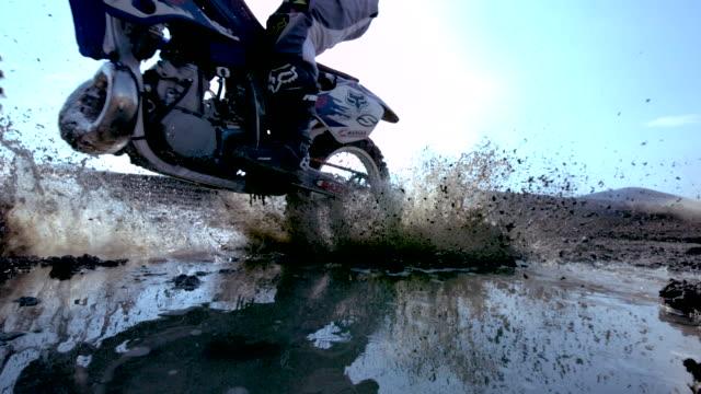 ms slo mo shot of dirt bike riding through puddle and splashing mud / venice, california, united states - motocross video stock e b–roll