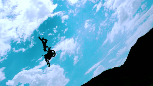 WS SLO MO LA DS Shot of dirt biker jump with one arm seat grab through air / Venice, California, United States