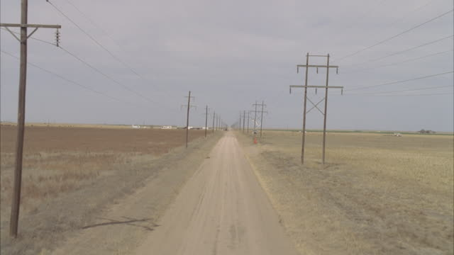 vidéos et rushes de ws ts aerial shot of dirt road, surrounded by fields and power lines, cherry picker and trailers in background / hooker, ok, usa - oklahoma