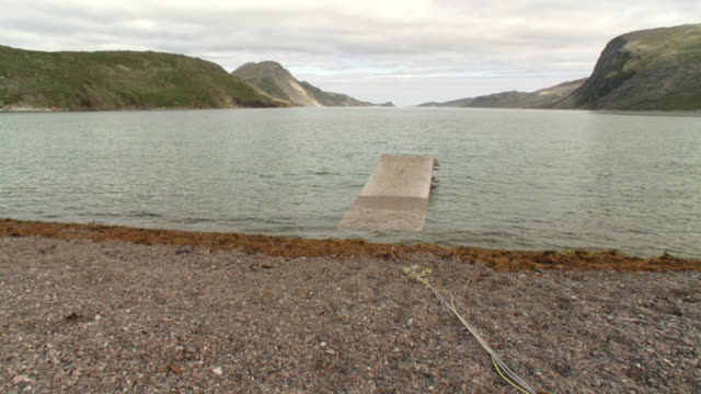 stockvideo's en b-roll-footage met ws shot of dock, rocks with water and mountains / torgat mtns, labrador, canada - wiese