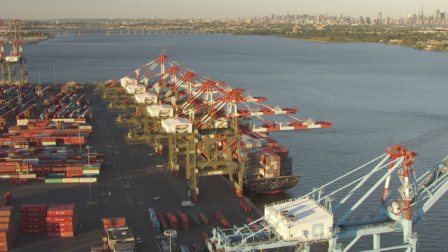 CU AERIAL ZO Shot of docked container ship at Elizabeth Marine Terminal at port Manhattan in in distance / Newark, New Jersey, United States