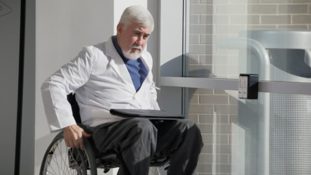 shot of doctor in wheelchair with muscular dystrophy using automatic door opener to exit from hospital - leaving hospital stock videos & royalty-free footage