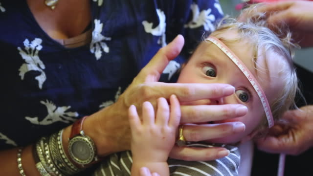 cu shot of doctor measuring baby's head / santa fe, new mexico, united states - messen stock-videos und b-roll-filmmaterial