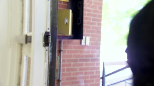 cu shot of door handle as several students pushing it open and walking out of building with door closing again / greensboro, north carolina, united states - 立ち去る点の映像素材/bロール