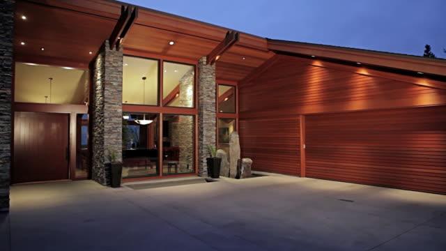 ms pan shot of door opening on modern home at dusk / lake oswego, oregon, united states - 建物入口点の映像素材/bロール