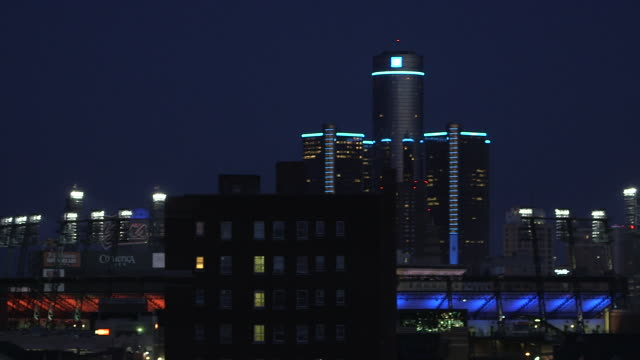 ms pan shot of downtown skyline at night with ford field, general motors renaissance center, and fox theatre / detroit, michigan, united states - デトロイト点の映像素材/bロール