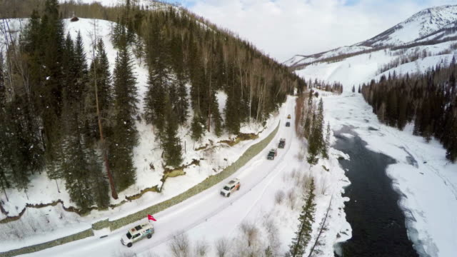 WS AERIAL shot of Driving On A Snowy Country Road nearby river/Xinjiang,China