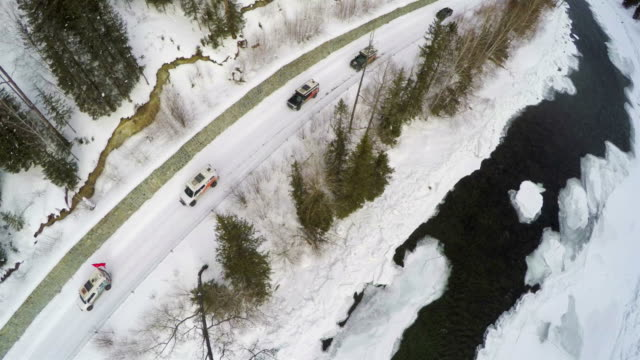 ws aerial shot of driving on a snowy country road nearby river/xinjiang,china - 新疆ウイグル自治区点の映像素材/bロール