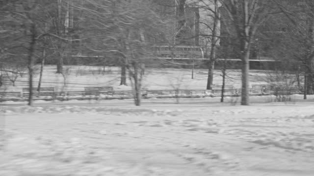 vídeos de stock e filmes b-roll de ms pov shot of driving through new york city in the snow from 60th street through the park - 1 minuto ou mais