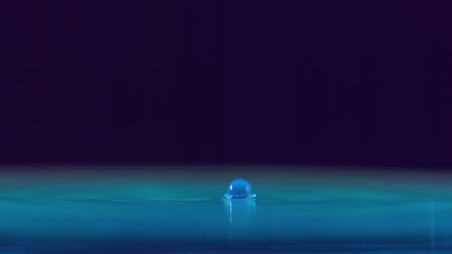 CU SLO MO Shot of Drop of water falls on surface of blue water / Toronto, Ontario, Canada