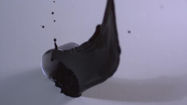 shot of dropping glass cup filled with black ink - spilling stock videos and b-roll footage