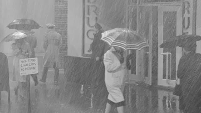 MS Shot of drug store entrance and Pedestrians walking rain