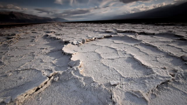 ws la pov shot of dry cracked earth and salt flats / death valley np, california, united states  - salt flat stock videos & royalty-free footage