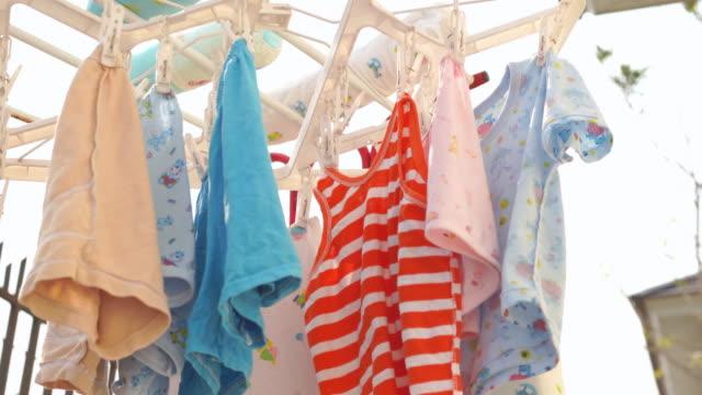 屋外のクリップにぶら下がっている乾燥赤ちゃんカラフルな服の4kショット。 - 物干し点の映像素材/bロール
