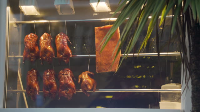 shot of ducks hanging from hooks in a window of a restaurant in london's chinatown district. - chinese food stock videos & royalty-free footage