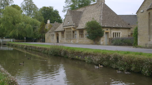ws shot of ducks in river to village waterside buildings  / upper  slaughter, gloucestershire, united kingdom   - gloucestershire stock videos and b-roll footage