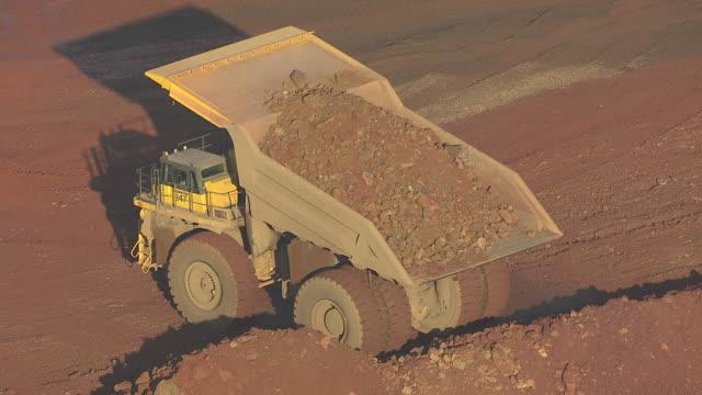 CU AERIAL Shot of dump truck dumps ore at Hull Rust Mahoning Mine / Hibbing, Minnesota, United States