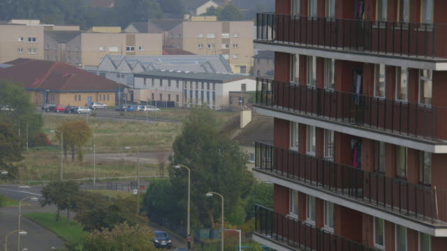 ms shot of edinburgh council estate with child throwing rocks on wall / edinburgh, edinburgh, united kingdom - 公営アパート点の映像素材/bロール